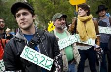 Occupy Wall Street demonstrators participating in a street-theater production wear signs around their neck representing their student debt during a protest against the rising national student debt in Union Square, in New York